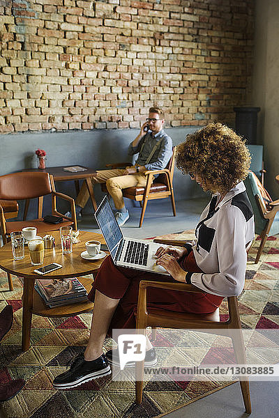Side view of businesswoman using laptop in hotel lobby