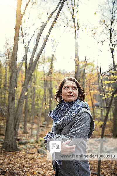 Thoughtful woman standing against trees in forest