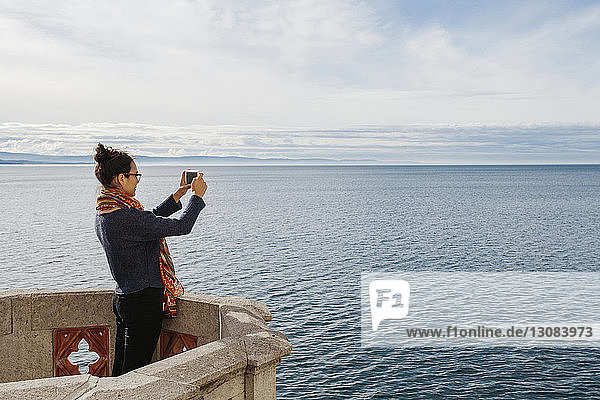 Side view of young woman photographing sea with smart phone while standing on building terrace against sky