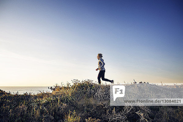 Full length of woman jogging on field against clear sky