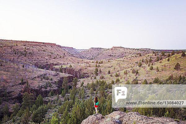 Rückansicht einer Frau  die auf einer Klippe vor Bergen und Himmel steht