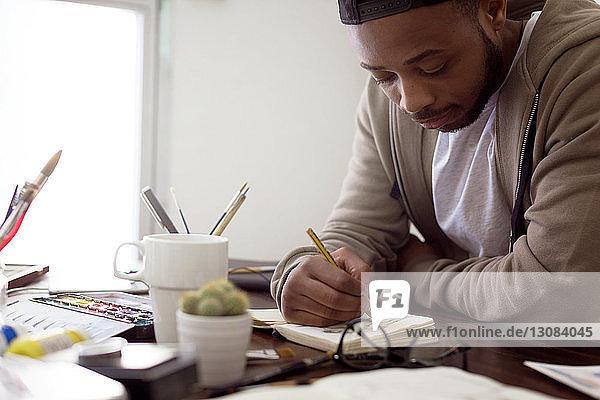 Junger männlicher Illustrator malt am Schreibtisch im Büro