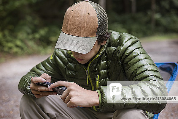 Hiker using phone while resting at camp site