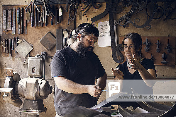 Coworkers discussing in blacksmith shop