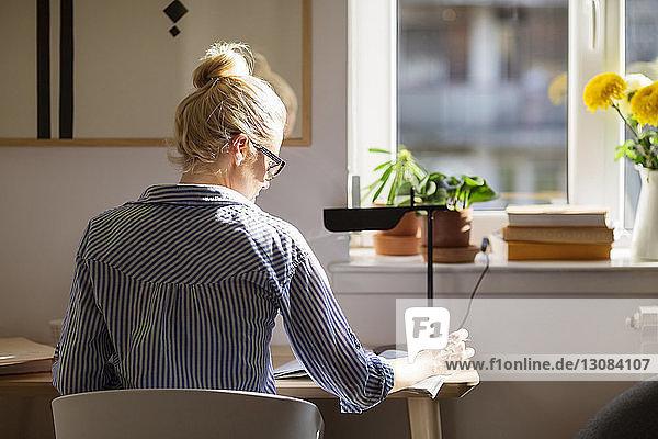 Rückansicht einer Frau  die am Tisch sitzend schreibt