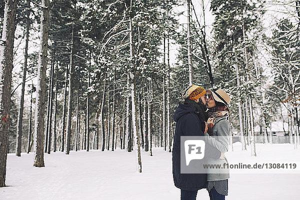 Romantisches Paar küsst sich stehend auf schneebedecktem Feld im Wald