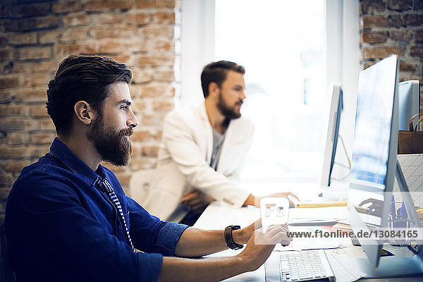 Male colleagues working in creative office
