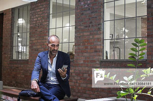 Geschäftsmann benutzt Smartphone  während er auf einem Sitz gegen ein Büro sitzt