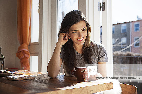 Glückliche Frau hält Kaffeetasse und sitzt zu Hause am Tisch