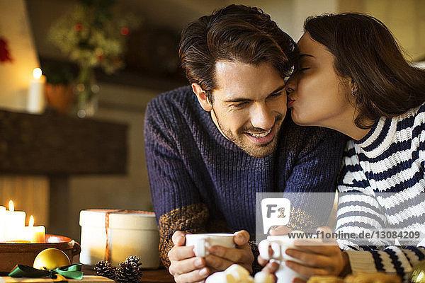 Frau küsst lächelnden Freund  während sie zu Weihnachten Kaffee bei Tisch trinkt