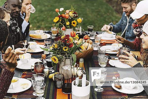 Friends eating food while sitting at table in backyard