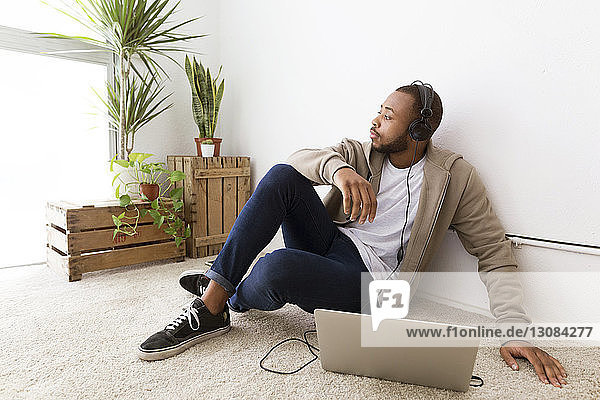 Businessman listening music while sitting on floor at creative office