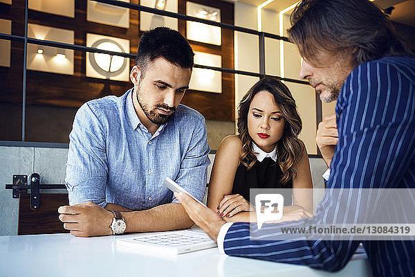 Geschäftsmann zeigt Kollegen digitales Tablett auf dem Schreibtisch