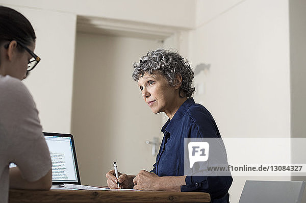 Mature woman writing while working with colleague at home