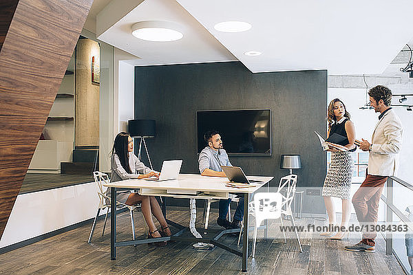Business people discussing at desk in illuminated office