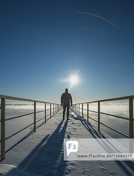 Rear view of man standing on snow covered pier over frozen lake against sky