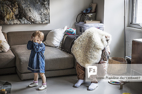 Vater und Tochter spielen zu Hause Verstecken