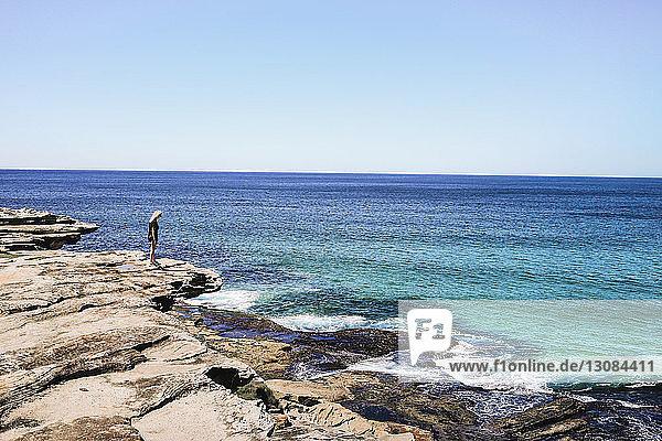 Frau steht auf Klippe gegen Meer und klaren Himmel