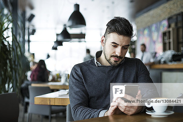 Mann benutzt Smartphone im Cafe