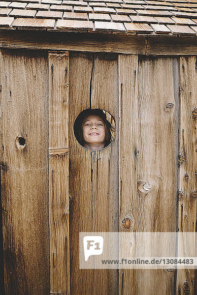Portrait of playful boy seen though wooden wall's hole