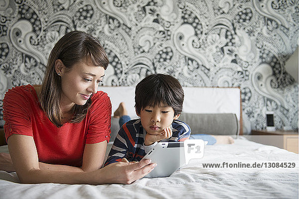Mother and son lying on bed and using digital tablet