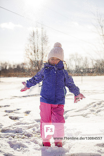 Portrait of girl standing on snowy field against sky