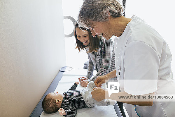 Doctor and woman playing with baby boy at hospital