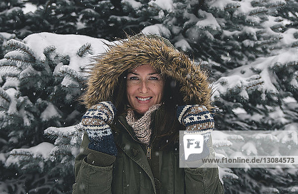 Portrait of cheerful woman wearing fur coat against trees during snowfall