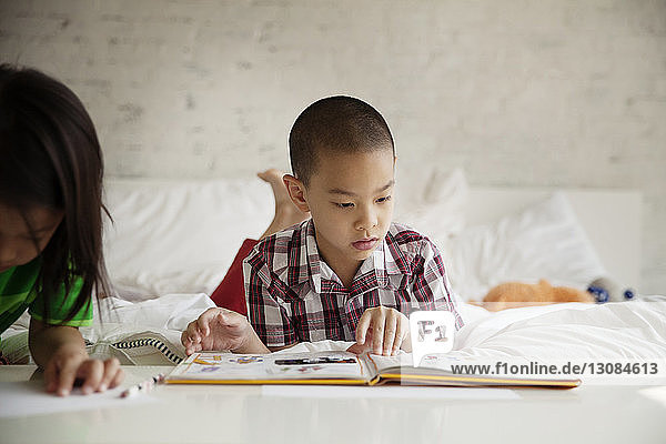 Boy reading picture book while lying besides sister on bed at home
