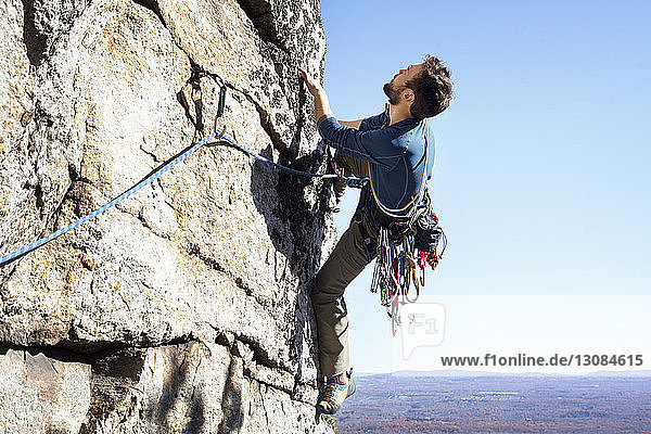 Mann klettert gegen klaren Himmel