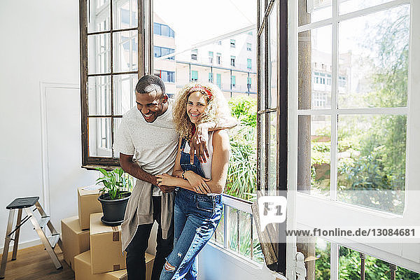 Portrait of cheerful wife standing with husband by window in new house