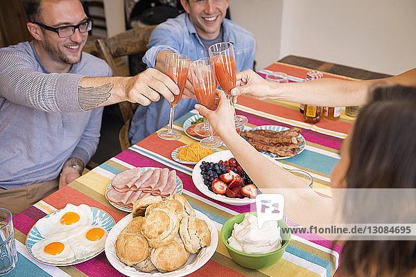 Freunde stoßen während des Essens zu Hause auf ein Getränk an