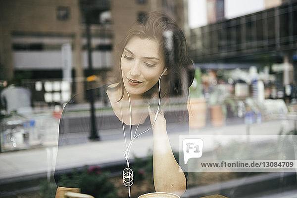 Frau benutzt Mobiltelefon  während sie im Café sitzt  durch Fenster gesehen