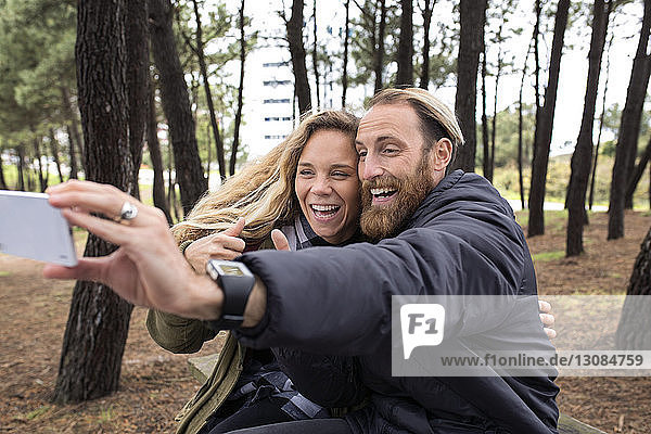 Cheerful couple taking selfie through smart phone in forest