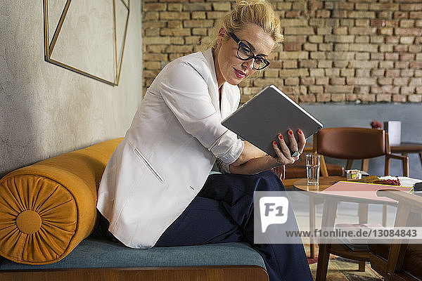 Businesswoman using tablet computer at hotel lobby
