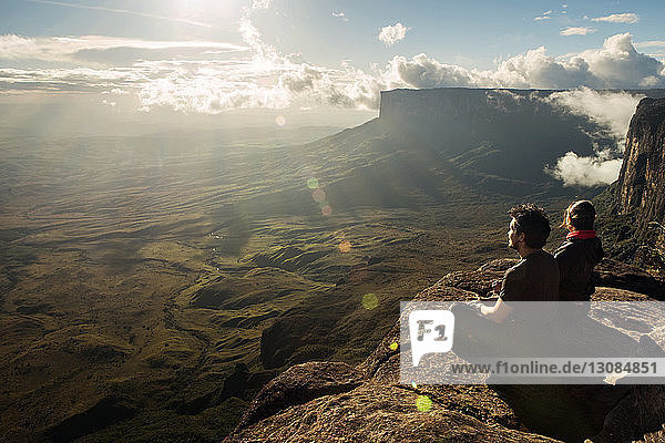 High angle view of friends sitting on cliff