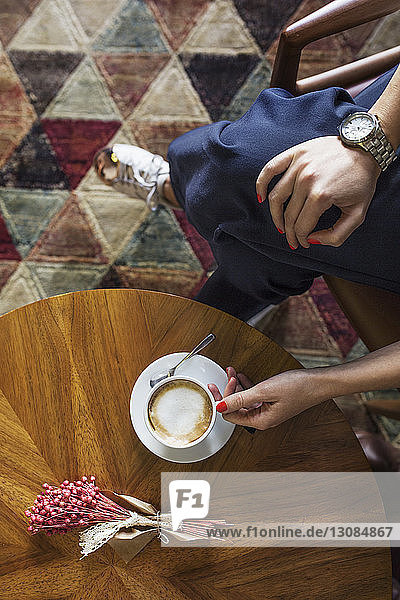 Overhead view of businesswoman holding coffee cup at hotel lobby