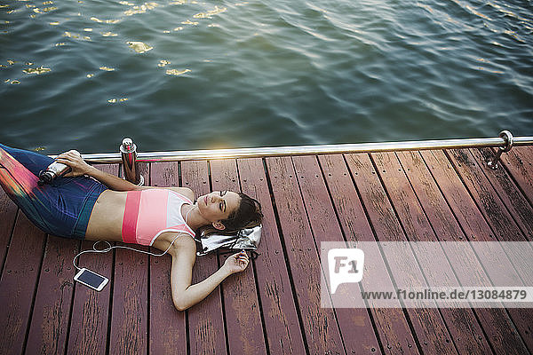 High angle view of woman listening music and relaxing on wooden walkway