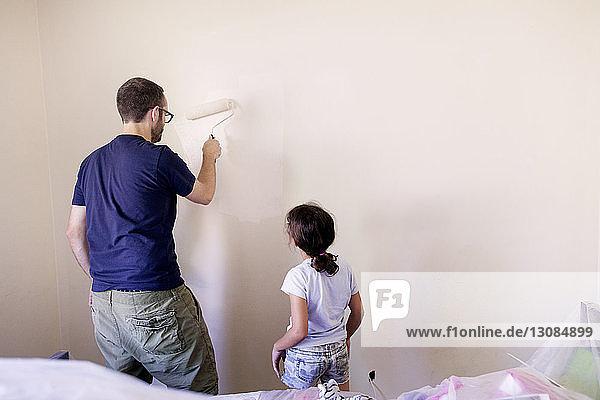 Mädchen betrachtet Vater bei Wandmalerei im Haus