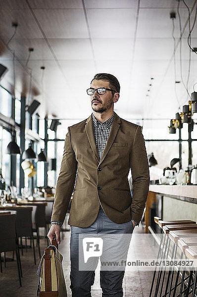 Selbstbewusster Geschäftsmann geht mit Aktentasche im Restaurant