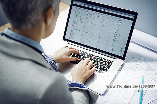 High angle view of female architect using laptop at table in office