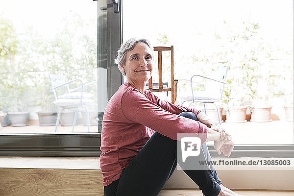 Side view portrait of happy mature woman sitting by window at home