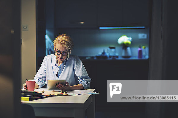 Businesswoman using tablet computer while sitting at desk in home office