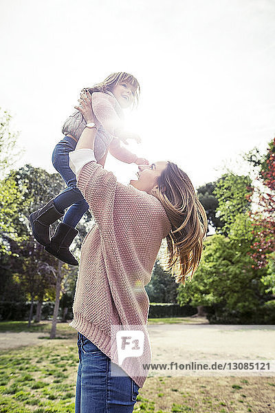 Side view of cheerful woman picking daughter at park