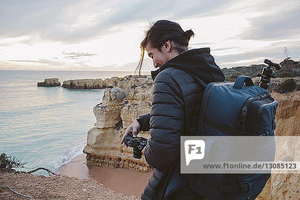 Seitenansicht eines Mannes  der eine Kamera hält  während er auf einer Klippe am Meer vor bewölktem Himmel steht
