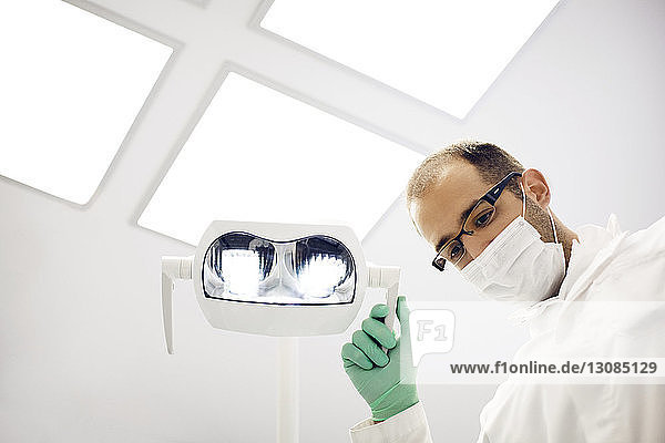 Low angle view of dentist adjusting lamp in clinic