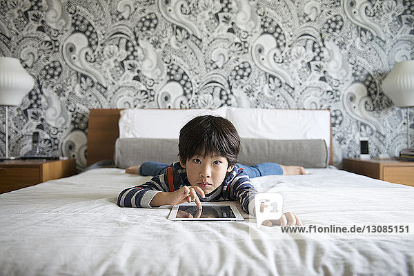Portrait of boy lying on bed and using digital tablet
