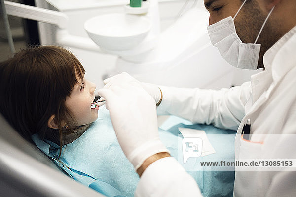 Male dentist analyzing girl's teeth at clinic