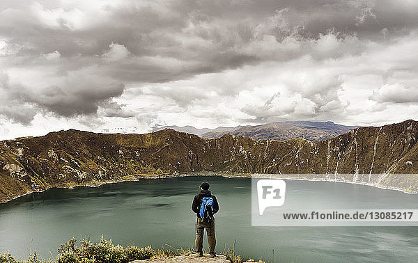 Rear view of man standing on cliff against Quilotoa and cloudy sky