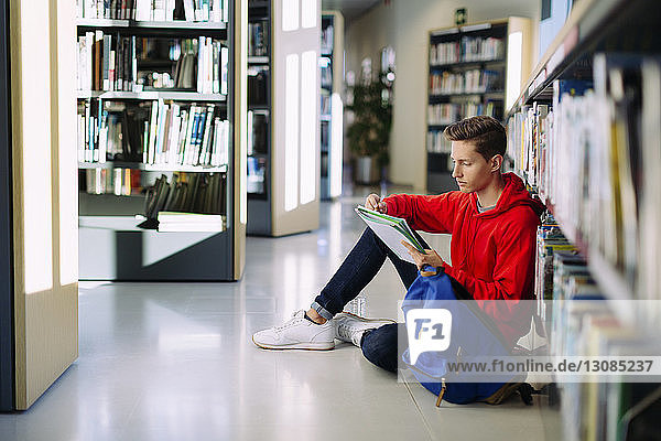 Mann lernt  während er in der Bibliothek auf dem Boden sitzt